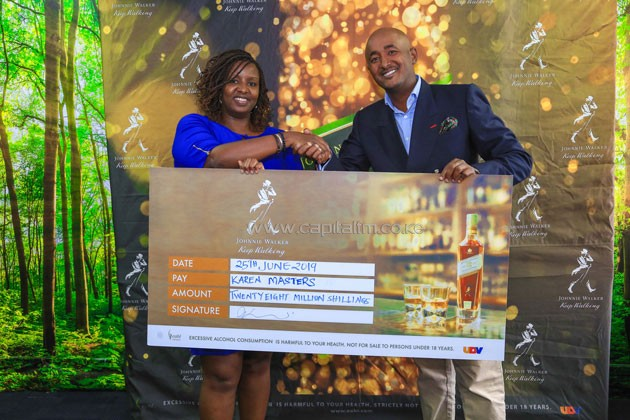 KBL Head of Spirits AnnJoy Muhoro (L) hands over a ceremonial cheque to Karen Country Club's Ali Mohammed during the Karen Masters sponsorship unveil.