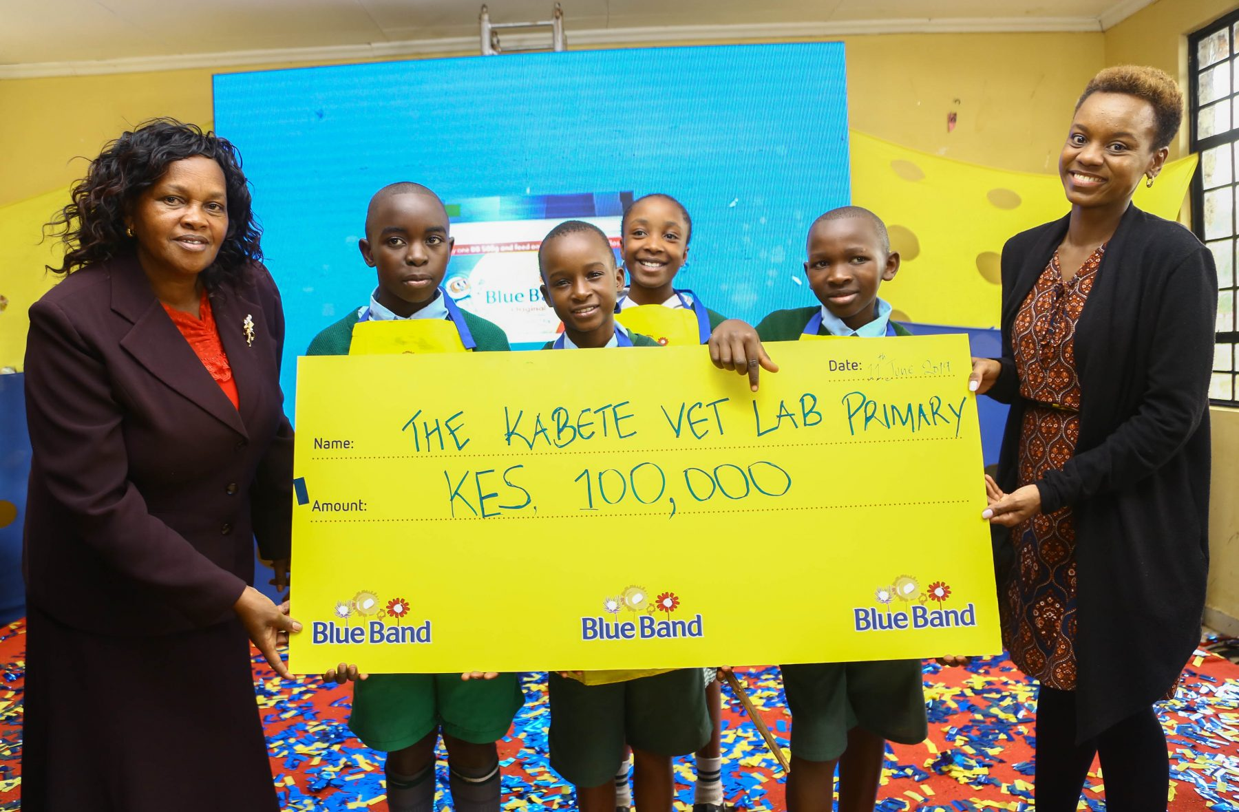 From left: Hellen Mugo, Head Teacher Kabete Vet lab primary School together with the students of Vet lab Primary School receive a dummy cheque worth Ksh. 100,000 from Jacky Mungai, Upfield Head of Marketing East and Southern Region during the launch of Blue Band Good Breakfast and Social Mission Campaign at Kabete Vet Lab Primary School.