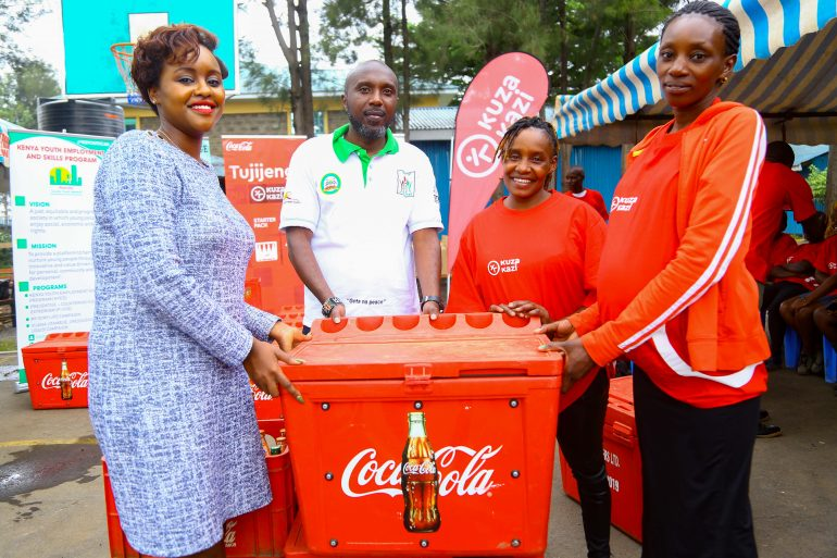Coca-Cola Sustainability Coordinator Public Affairs and Communications, Victoria Macharia (Left), in company of One-Stop Youth Program Coordinator, Wainaina Muiruri (second left), present a Coca-Cola sales starter pack inclusive of a cooler box and crates of Coca-Cola beverages to Kuza Kazi beneficiaries, Wincete Karemi (Right) and Doreen Omwenga.