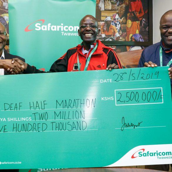 Joseph Ogutu, Safaricom's Chief Special Projects Officer (left) presents a dummy cheque of KES 2.5Million to Benard Banja Secretary General, Deaf Athletics Association of Kenya (DAAK) and Tom Okiki Public Relations Officer (DAAK) ahead of the upcoming Kericho Deaf Half marathon slated for 16th June.