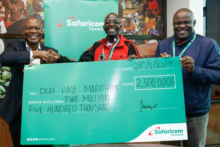 Joseph Ogutu, Safaricom's Chief Special Projects Officer (left) presents a dummy cheque of KES 2.5Million to Benard Banja Secretary General, Deaf Athletics Association of Kenya (DAAK) and Tom Okiki Public Relations Officer (DAAK) ahead of the upcoming Kericho Deaf Half marathon slated for 16th June.